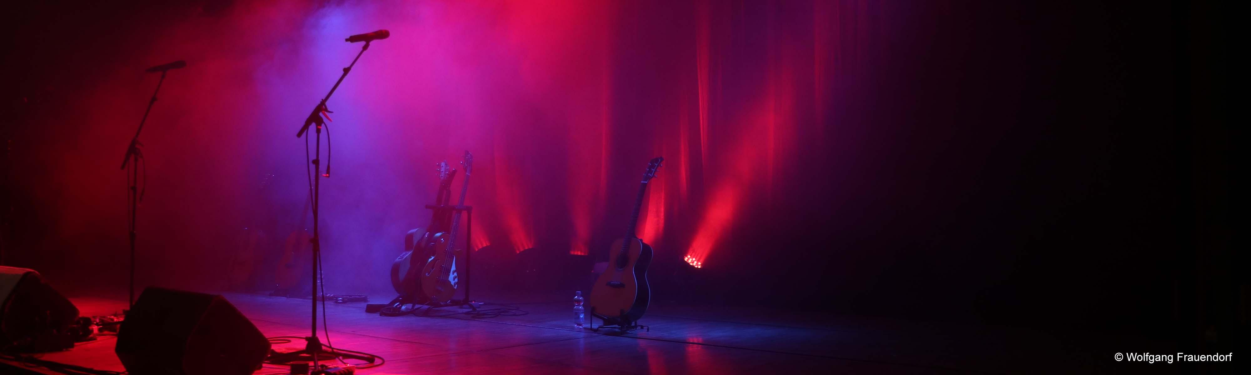Bühnenbild mit roten Scheinwerfern Gitarren Mikrofone